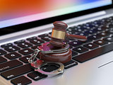Handcuffs and judge gavel on the laptop keyboard
