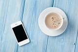 Coffee cup and smartphone on wooden table background
