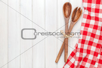 Kitchen utensils over white wooden table background