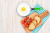 Healthy breakfast with fried egg, tomatoes and toasts