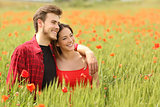 Couple hugging and walking in a green field