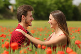 Couple looking each other affectionate in a red field
