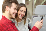 Couple of passengers sharing a smart phone inside a train