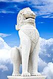 Antique guardian lion sculpture on blue sky background.