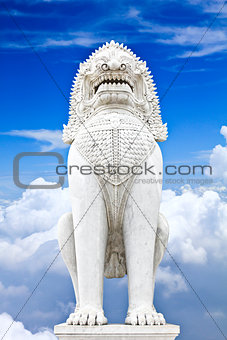 Antique guardian lion sculpture on blue sky background.