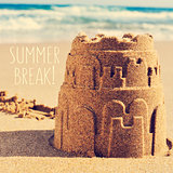 sandcastle on a beach and the text summer break