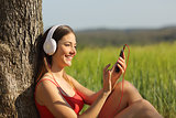 Girl listening to the music and downloading songs in a field