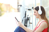 Woman listening to the music from a tablet in a park