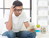 Stressed Indian guy counting money