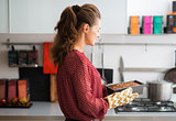 Woman in profile standing in kitchen holding hot loaf tin