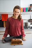 Woman smiling while standing in kitchen over fresh baking