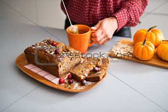 Sliced home-made loaf of pumpkin bread, woman's hands and tea