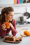 Woman smiling in kitchen holding mug with fresh fruit loaf
