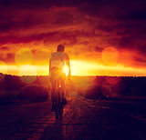 Man Riding a Bicycle at Sunset