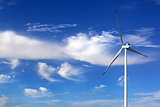 Wind turbine and blue sky with clouds