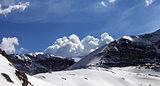 Panoramic view on snow rocks and cloudy blue sky