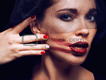 beauty brunette woman under black veil with red manicure close up