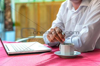 breakfast businessman with a laptop in a cafe