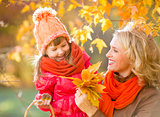 Smiling mother and kid outdoor with autumn yellow leaves