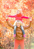 Happy parent and kid walking in fall outdoor