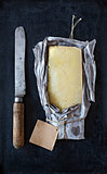 Mature cheddar cheese wrapped in rustic paper and a vintage knife.