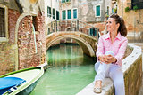 Woman sitting by canal in Venice