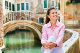 Closeup of happy woman smiling by canal in Venice