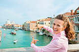 Laughing woman tourist in Venice framing shot of Grand Canal