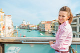 Smiling woman tourist standing above Grand Canal in Venice