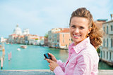 Smiling woman tourist holding camera above Grand Canal
