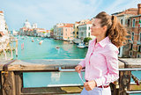 Woman tourist in profile standing holding map above Grand Canal