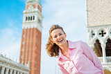 Happy woman tourist with St. Mark's bell tower and Doge's Palace