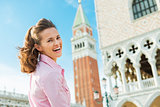 A happy woman tourist looking over shoulder in St Mark's Square