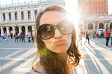 Woman tourist on St. Mark's Square taking selfie blowing a kiss