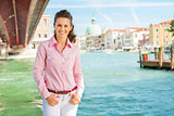 Happy, relaxed woman tourist standing near Grand Canal in Venice