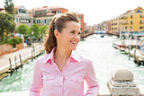 Happy woman smiling, looking into distance on bridge in Venice