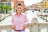 Smiling woman leaning against bridge in Venice