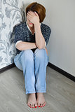 Woman with depression sitting in the corner of  room