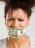 Covering mouth with a dollar banknote