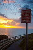 flocks of starlings above warning sign