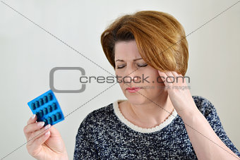 Adult woman taking a pill for  headache
