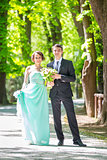 Wedding couple walking in park.