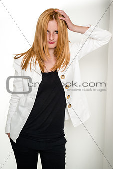 Beautiful young woman leaning against wall