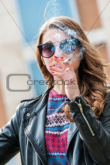 Beautiful female smoking a cigarette with smoke in front of face.
