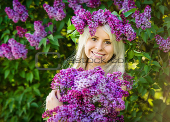 Beautiful smiling young woman is wearing wreath of lilac flowers