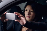 Woman taking a selfie as she waits in her car