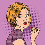 Beautiful girl paints her lips red lipstick pop art comics retro