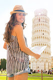 Smiling woman tourist holding map at Leaning Tower of Pisa