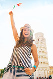 Happy woman tourist waving flag at Leaning Tower of Pisa