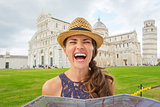 Laughing woman tourist holding map in near Leaning Tower of Pisa